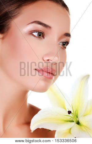 Face of a beautiful girl with a fresh flower lily, isolated on white background