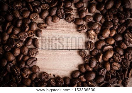 roasted coffee beans on wooden background can be used as a background