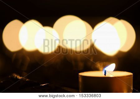Burning candle against defocused background of candlelight