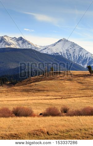 Mountain landscape with snow-capped mountains and large valley.