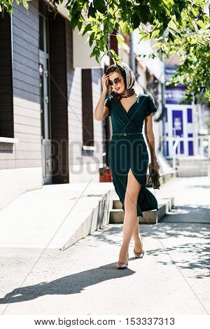 Young stylish woman in sunglasses walking on the street