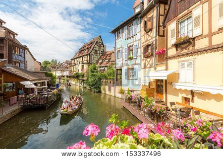 COLMAR - JUL 13: Unidentified tourists riding boat in La Lauch at La Petite Venise on JUL 13, 2015. Colmar is situated on the Alsatian Wine Route and considers itself to be capital of Alsatian wine.
