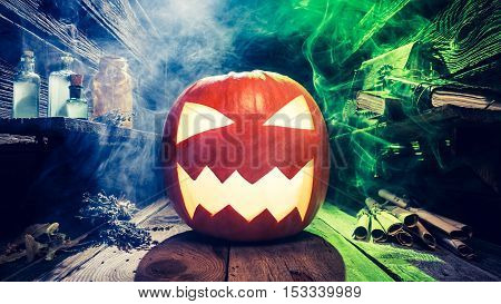 Glowing Halloween pumpkin in witcher cottage on old wooden table