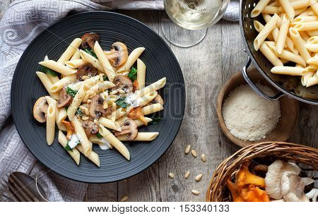 Pasta with seasonal mushrooms on rustic tabletop. Horizontal, view from above.