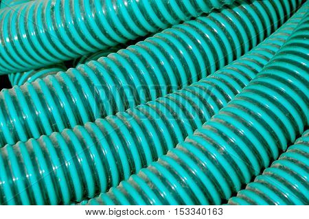 Green plastic pvc  ppr pipes hose for plumbing water fluids hydraulic sewage on the floor of construction site. background