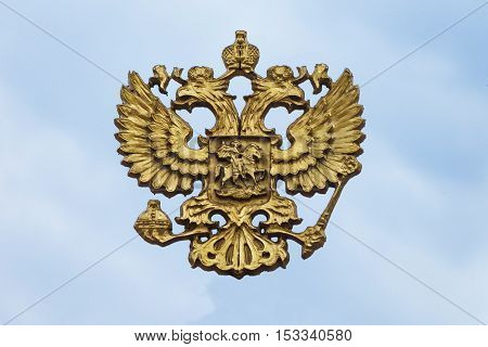 Cast bronze Russian coat of arms on the background of the sky. Russian State Emblem - a double headed eagle.