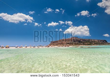 Balos lagoon on Crete island, Greece. Tourists relax and bath in crystal clear water of Balos beach.