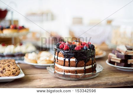 Brown wooden table with naked cake with chocolate and berries, cookies and tarts. Candy bar. Studio shot.