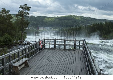 STORFORSEN, SWEDEN ON AUGUST 20. View of a bridge, rapids and the Hotel on August 20, 2016 in Storforsen, Sweden. Red and white float on the fence. Forests and hills. Editorial use.