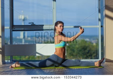 fitness, sport, training and lifestyle concept - smiling woman stretching on mat in gym. light from a large window selfie