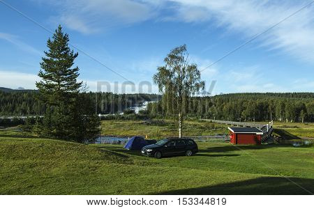 STORFORSEN, SWEDEN ON AUGUST 21. View of a campsite, bridge, forest and the river on August 21, 2016 in Storforsen, Sweden. Morning view from the Chapel Hill. Editorial use.