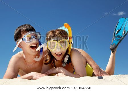 Portrait of cheerful couple in aqualungs lying on sand
