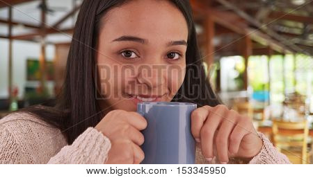 Young Latino Woman Enjoying Warm Cup Of Coffee In Café