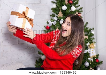 Young Surprised Woman Opening Gift Box Near Decorated Christmas Tree