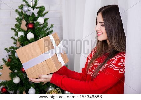 Surprised Young Woman With Gift Box And Christmas Tree
