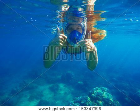 Snorkeling woman underwater showing thumbs. Snorkel in full face mask. Female swimmer with loose red hair. Beautiful girl in water. Underwater photo shot in ocean. Tropical vacation activity or sport
