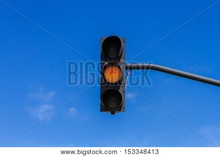 Traffic light with yellow light on and blue sky background