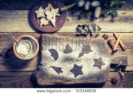 Decorating with icing sugar Christmas gingerbread cookies on wooden table