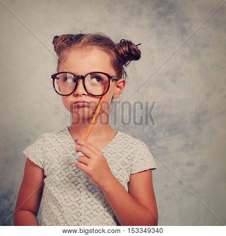 Thinking Grimacing Kid Girl In Glasses Looking Up And Have An Idea, Holding Pencil In Hand On Blue B