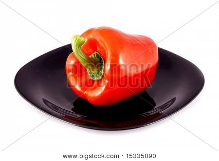 Red paprika pepper on black plate isolated on white