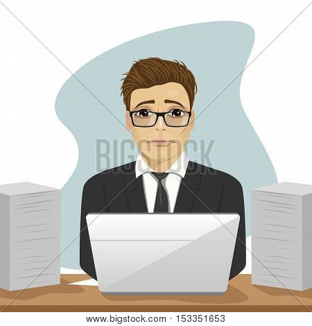 young sad businessman working hard surrounded with paper documents and laptop in office