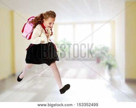 Pretty little girl schoolgirl in white blouse and black skirt to hurry to school. She jumps over the obstacle.In the room with the big bright window in the wall.