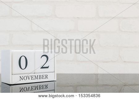 Closeup white wooden calendar with black 2 november word on black glass table and white brick wall textured background with copy space selective focus at the calendar