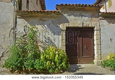 An old wooden door in Valvasone in Friuli Venezia Giulia north east Italy.