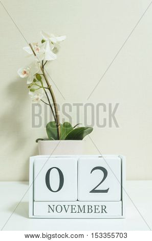 Closeup white wooden calendar with black 2 november word with white orchid flower on white wood desk and cream color wallpaper in room textured background selective focus at the calendar