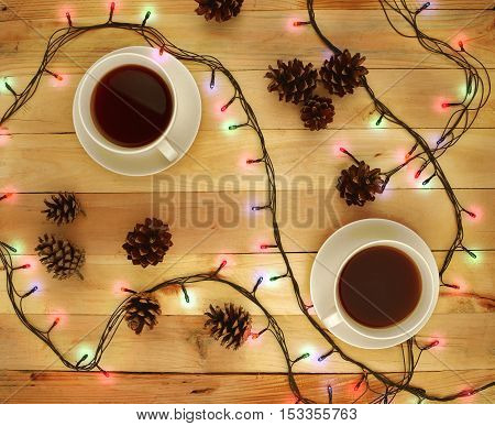 Two cups of hot drink on a wooden background. Top view. Tea. Coffee. Garlands . The lights cones. The festive mood. Break. Home comfort. Christmas atmosphere. Night. Love. Friends. Time for two.