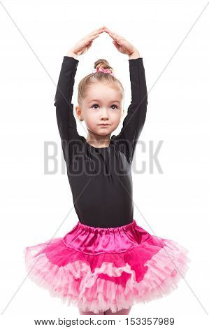 Little dance girl in pink tutu on isolated background stands in dancing pose putting her hands up