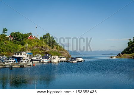 House on the hill and small motor boats docked at pier. Falkensten, Norway.