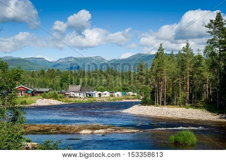 Norwegian camp on the river landscape. Forest, fast river and mountain range at the background.