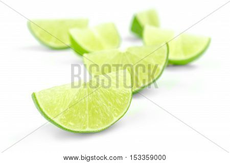 scattering of fresh lime wedges isolated on a white background.