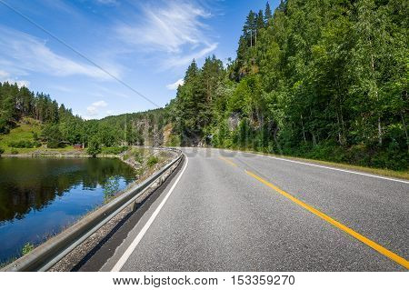 Country landscape with lake's shore and empty highway road. Norway.