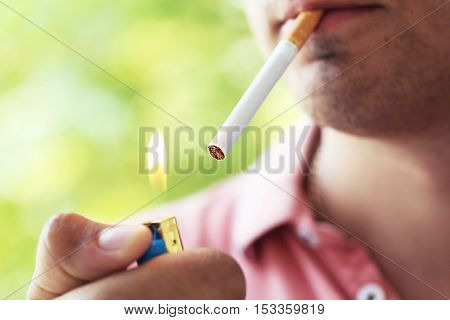 Man holding and lighting up cigarette, close up