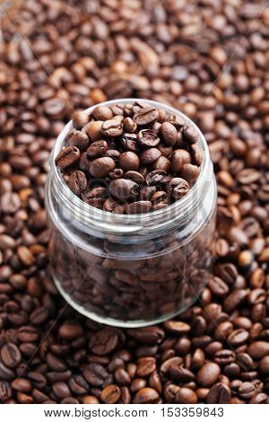 Brown roasted coffee beans in jar, close up