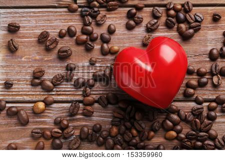 Roasted Coffee Beans With Red Heart On A Brown Wooden Table
