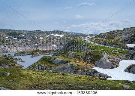 Scenic Norwegian landscape with rocks, lake and curved mountain road with some cars on it. Norway.