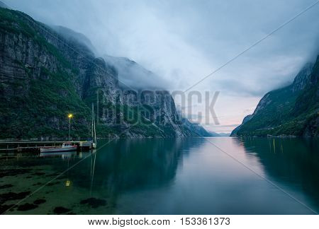 Night landscape of beautiful Norway fjord between the mountains. Lantern on the docked fishing boat. Lysefjord, Norway.