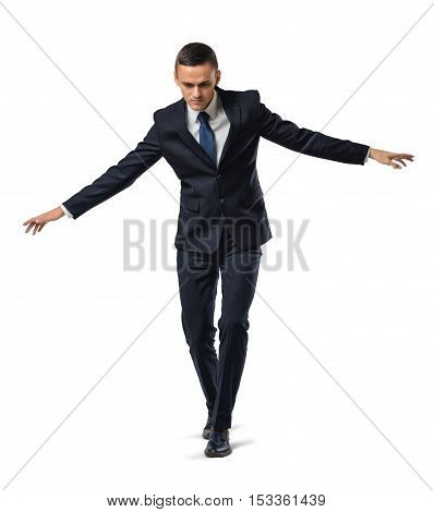 Portrait of a businessman walking a tightrope or border, isolated on a white background. Keeping balance. Acting carefully. Being very cautious. Concentration and attention.