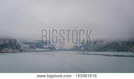 Panoramic norwegian fjord seascape with deep fog and clouds hiding the mountain peaks. Lysefjord, Norway.