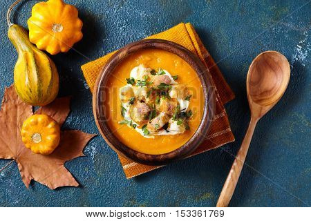 Pumpkin and carrot soup with cream, parsley, croutons for Thanksgiving, halloween. On dark blue creative background. Top view. Composition of autumn vegetables.