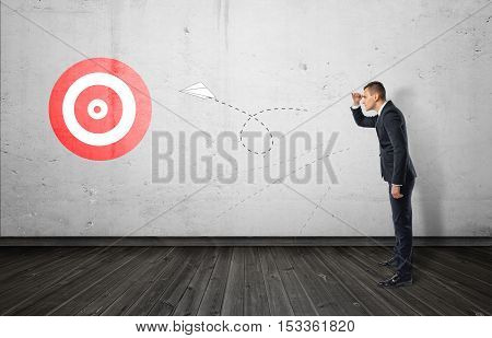 Businessman keeping track of the paper airplane flying right on target. Long-term plan. Distant goal. Total control.