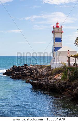 lighthouse on ocean coast in bay cascais in summer day