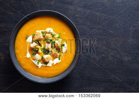 Vegetable cream pumpkin soup with carrot and cream. Top view on a dark creative background. Healthy diet meal.