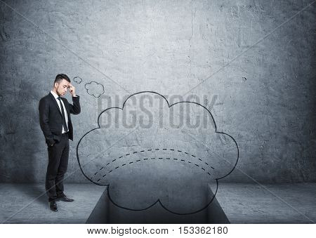 Full growth portrait of a businessman imaging a bridge over a gap on a grey background. Finding a way to solve a problem. Facing difficulties. Handling a hopeless situation.