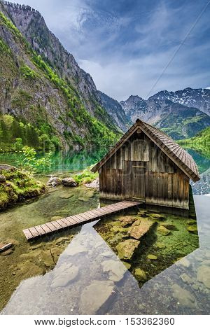 Mirror Reflection A Wooden Cottage At The Obersee Lake In Alps, Germany