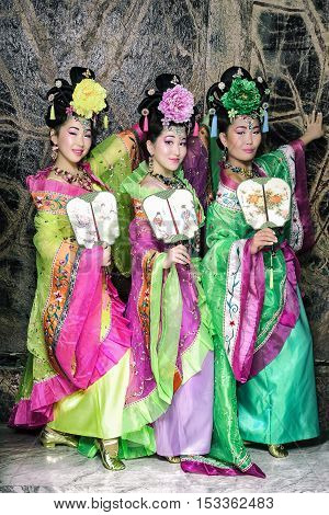 Three fashion geishas standing with fans against the marble wall