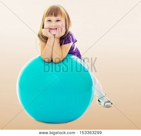 On a brown background a smooth transition from dark to light. About what dreams a little girl , put his hands on big blue fitness ball.